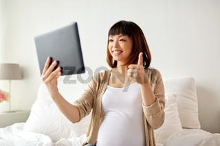 happy pregnant asian woman with tablet pc at home