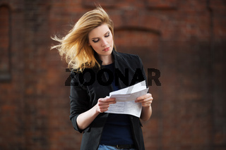 Young business woman reading a tax letter on city street