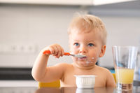 Adorable one year old baby boy eating yoghurt with spoon