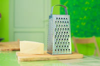 A metal grater and a cut piece of cheese lie on a wooden board