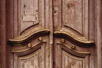Close-up Wooden ancient Italian door in the historic center. Old European architecture. Two-fold wooden carved door. Vintage concept in architecture