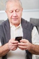 Senior liest SMS auf dem Smartphone
