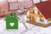 Schlüsselanhänger mit Herz auf Bauplan mit Modellhaus