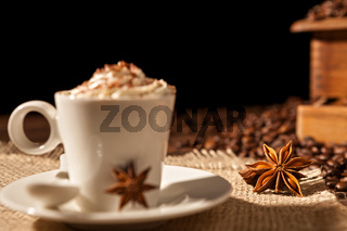 Close-up of coffee cup with whipped cream and star anise