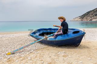 Teenage boy rowing in boat on greek beach