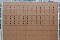 brown panels with a set of square holes on the wall of a shopping complex during repairs.