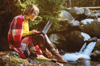 A toned portrait of a a smiling freelancer hipster girl with glasses dressed in a blanket with a laptop kneeling sitting on a rock in a coniferous forest next to a stormy mountain river in warm sunlight. The concept of freelancing work at a distance and t