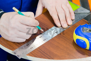 Close-up Men's hands draw a pencil on the ruler with a sub-standard template for cutting out furniture details next to the jigsaw and furniture clips