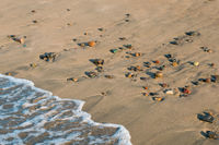 wave hits beach with colorful pebble stones - closeup