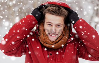 happy man in winter jacket with hood outdoors