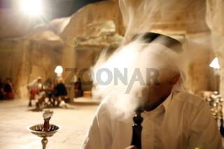 Ein Beduine raucht in der Cave Bar eine Wasserpfeife