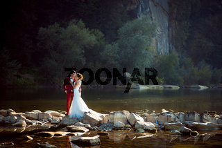 Horizontal full-length wedding portrait of the fashionable newlyweds tenderly hugging on the riverstones during the sunset.