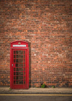 British Phonebox Against Red Brick Wall