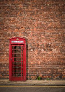 British Phonebox Against Red Brick Wall