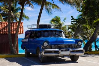 Amerikanischer blauer Mercury Oldtimer parkt am Strand unter Palmen in Varadero Cuba - Serie Cuba Reportage