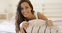 Happy attractive woman relaxing on her bed