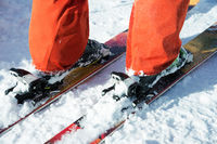 Orange alpine ski boots in a ski mount. One boot is completely fixed on skis, the second is not.