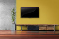 Living room led tv on yellow wall with wooden table media furniture