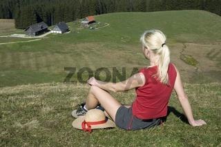 Eine blonde Frau macht vom Wandern Rast in einer Almwiese im Nationalpark Kalkalpen und schaut auf die Ebenforstalm