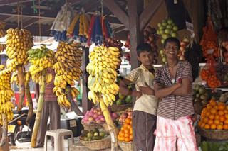 Junge Verkäufer und ihr Stand mit Obst und Bananen auf dem Markt in Galle