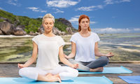 women meditating in yoga lotus pose outdoors