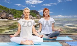 women meditating in yoga lotus pose outdoors