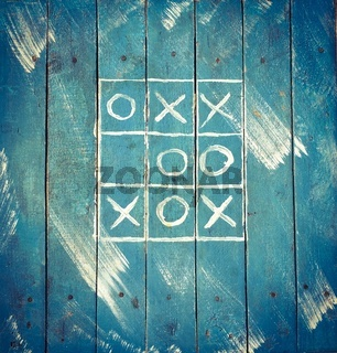 Tic tac toe on a blue wooden old board