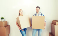 smiling couple with big boxes moving to new home