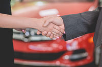 Vehicle dealer shaking hand with young woman.