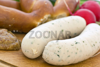 Weisswurst with Pretzel and sweet mustard  as closeup on a chopping board