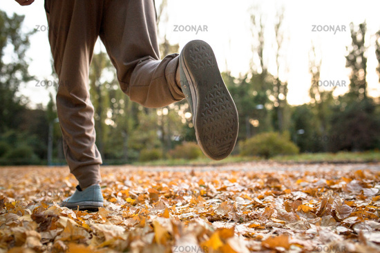 Close up view of man running on dried autumn leaves.