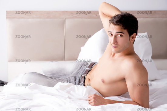 Young handsome shirtless guy showing nude torso sexy on bed at h