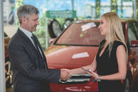 Happy young female shaking had with auto dealer.