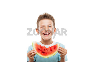 Handsome smiling child boy holding red watermelon fruit slice