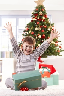 Happy kid raising arms at christmas