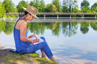 Woman writing at waterside in nature