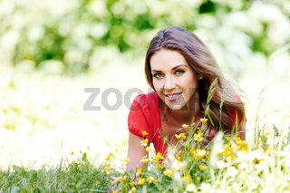 young woman in red dress lying on grass