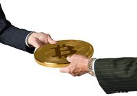 Two traders hands holding large bitcoin