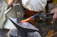 Blacksmith hammering hot metal arrow