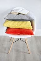 Close up of the chair in an interior with pillows in trendy colors and book on them
