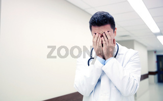 sad or crying male doctor at hospital corridor