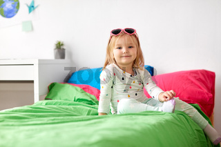 smiling little girl with sunglasses on bed at home
