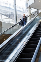 Businesswoman with large black bag and mobile phone descending on escalator.