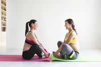 Two young pregnant women doing fitness exercises