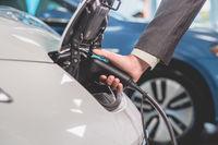 Close up view of man recharging electric car.