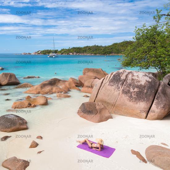 Woman sunbathing at Anse Lazio picture perfect beach on Praslin Island, Seychelles.