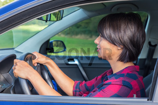 Woman behind steering wheel in car