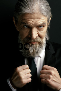 Grey haired old man with strict look.