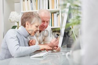 Paar Senioren macht Shopping am PC