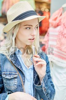 Junge Frau mit Kreditkarte überlegt